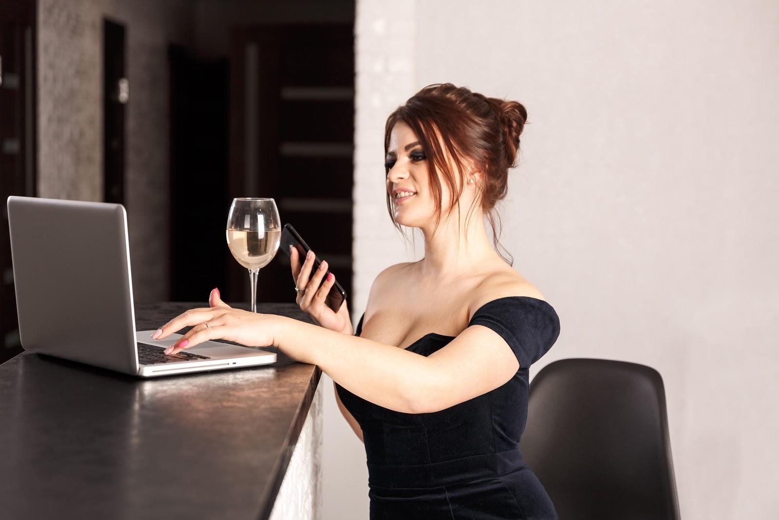 Woman in a fancy dress sitting in front of her laptop