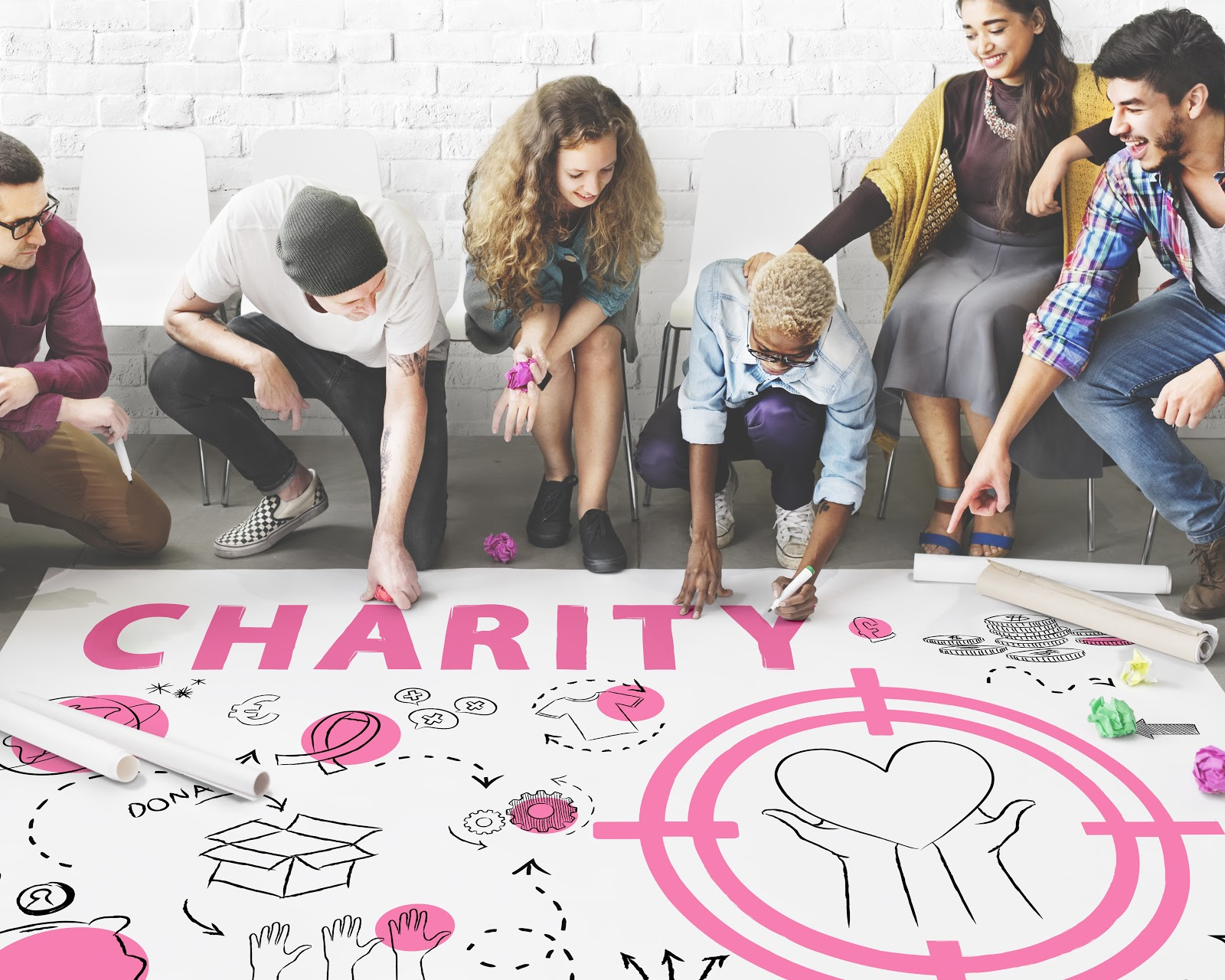 """Virtual fundraising events: Group of people drawing on large poster that reads """"Charity"""""""