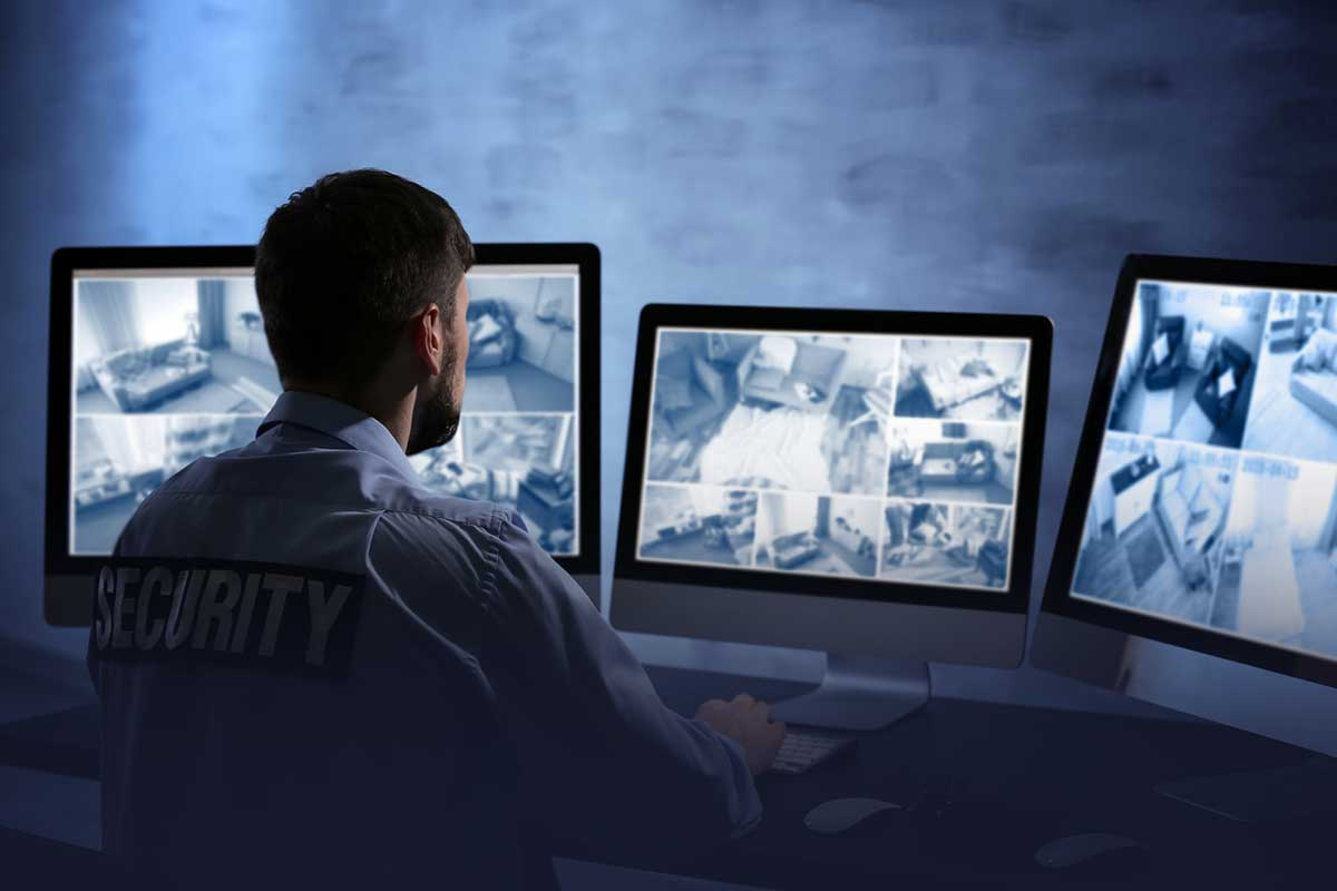 Security officer looking at several computer monitors