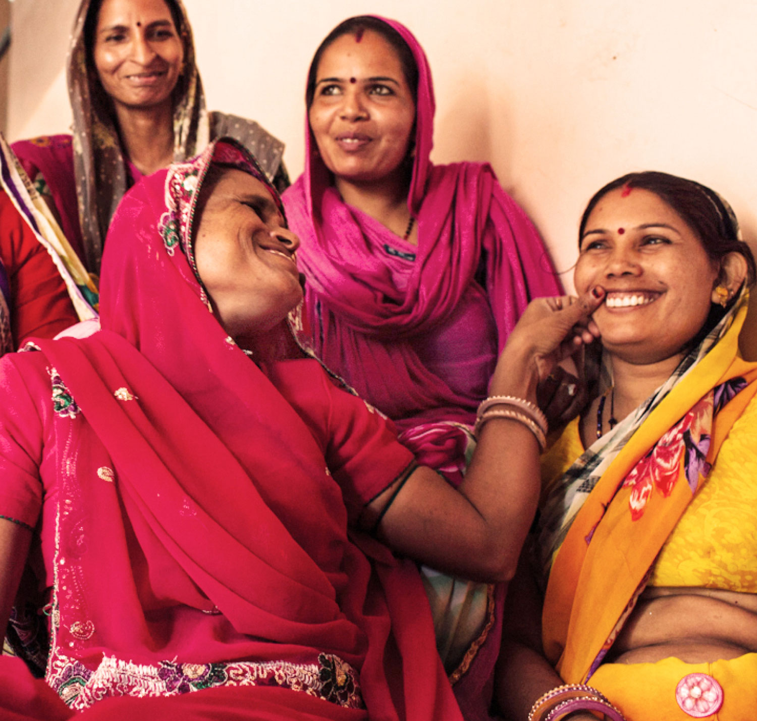 Four women smile at each other