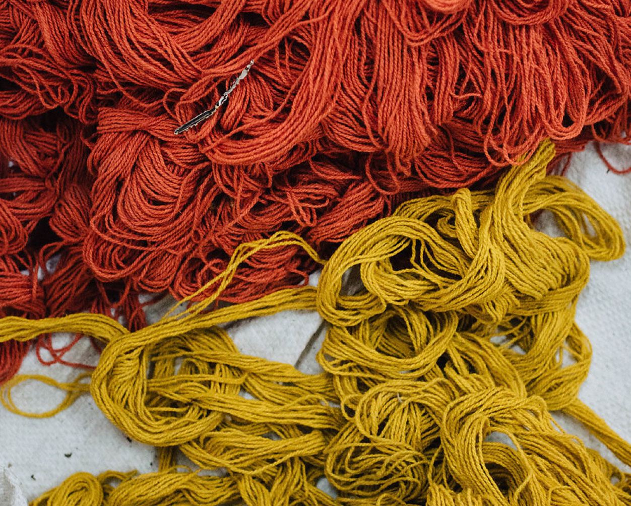 A close-up picture of orange and yellow thread.