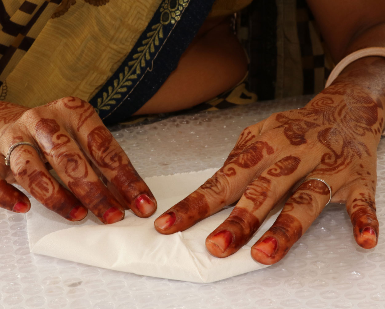 A close-up picture of hands folding a piece of white fabric.