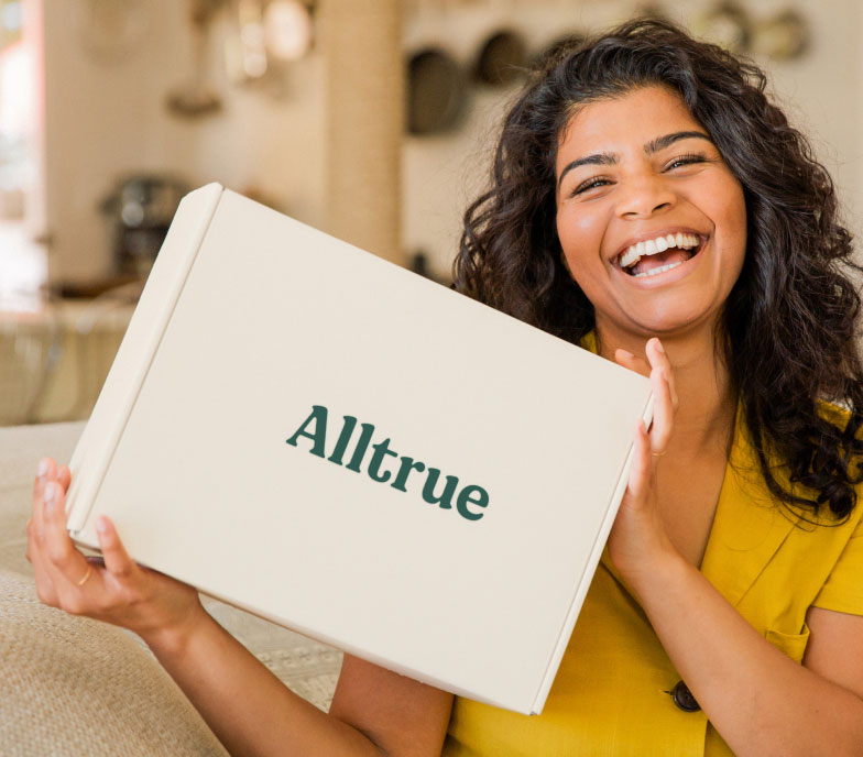 Woman holding an Alltrue box and smiling