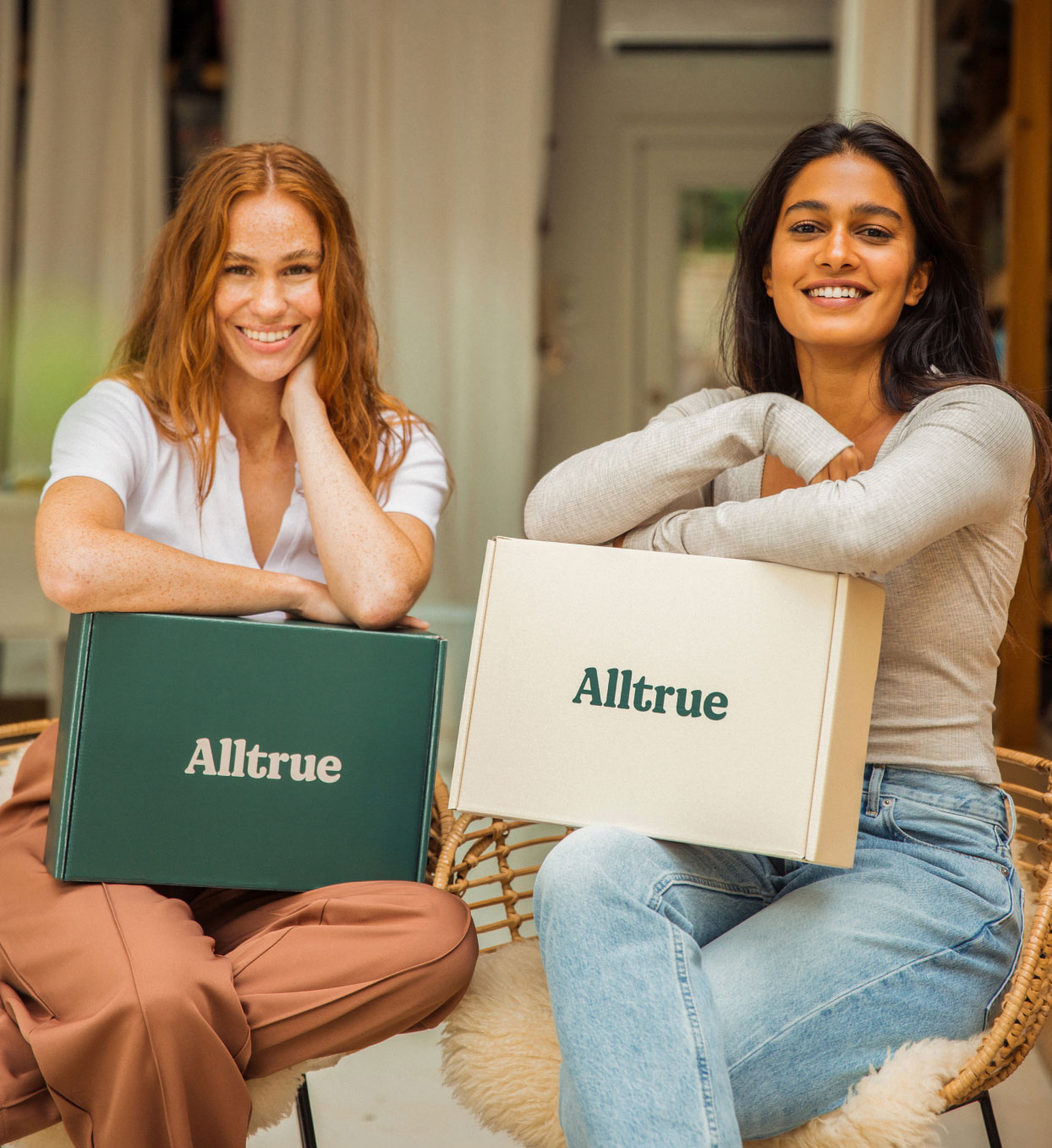 Two women smiling and looking at the camera. Both have an Alltrue box on their laps.