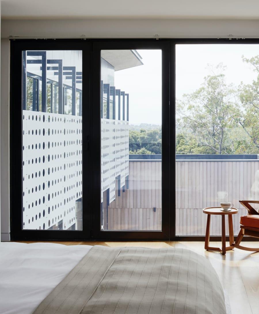 Chambre avec une grande baie vitrée donnant sur un bâtiment et des arbres