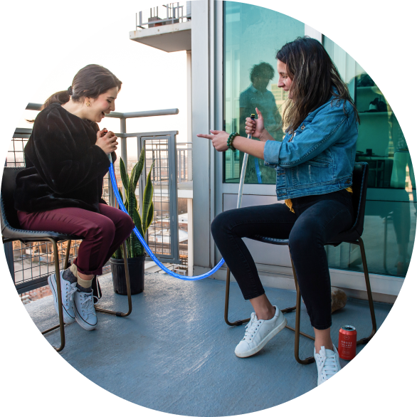 Two women having fun playing light pong on their apartment balcony.