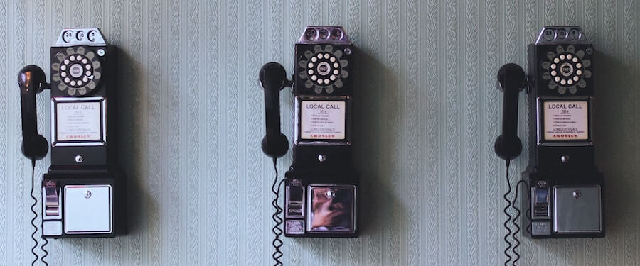 three old telephones hanging on the wall travel nursing phones interview