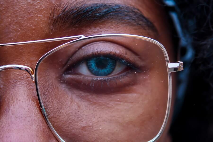 woman looking into camera closeup of her eye blue light glasses