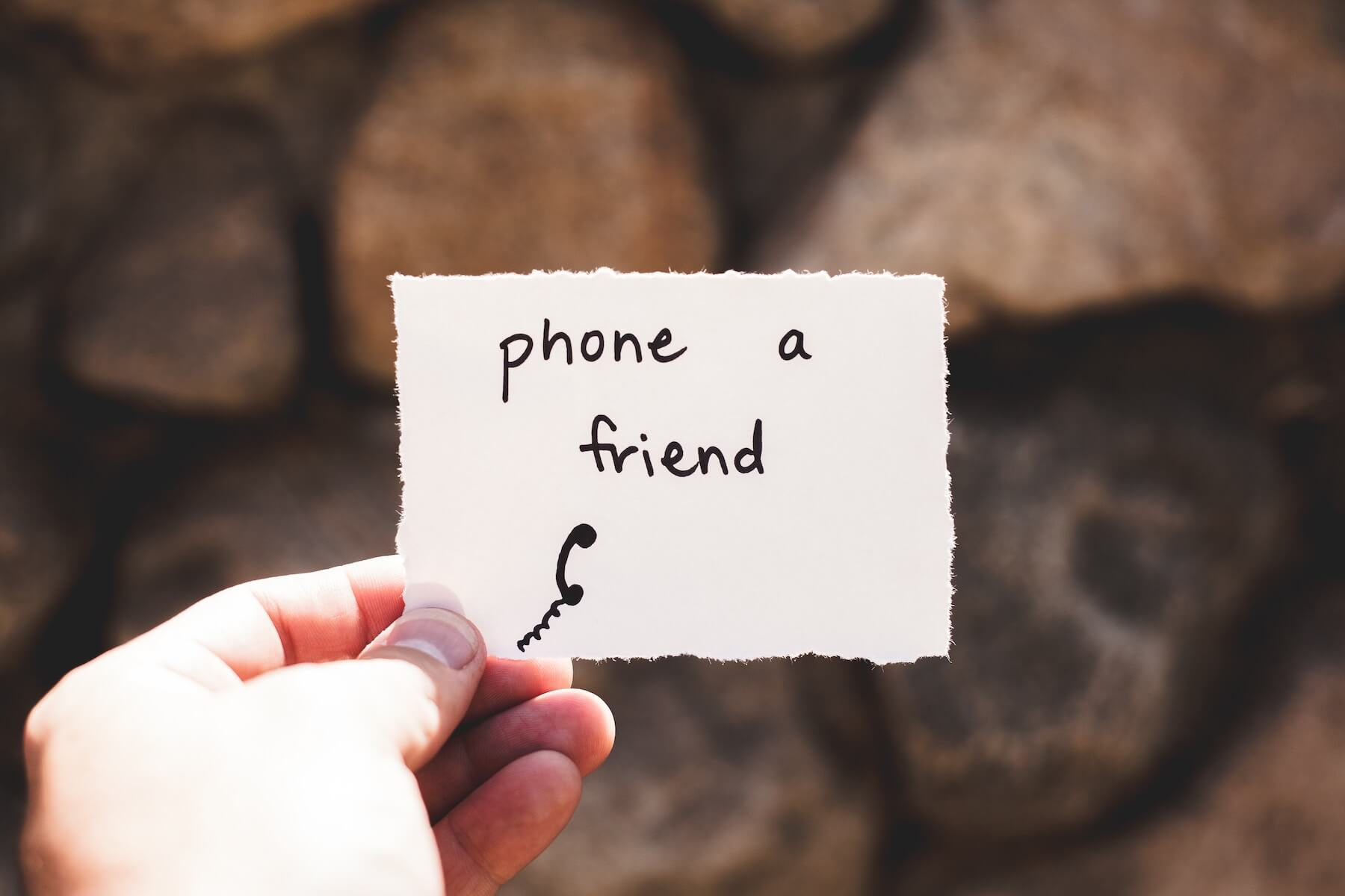 hand holding piece of paper says phone a friend nursing ptsd