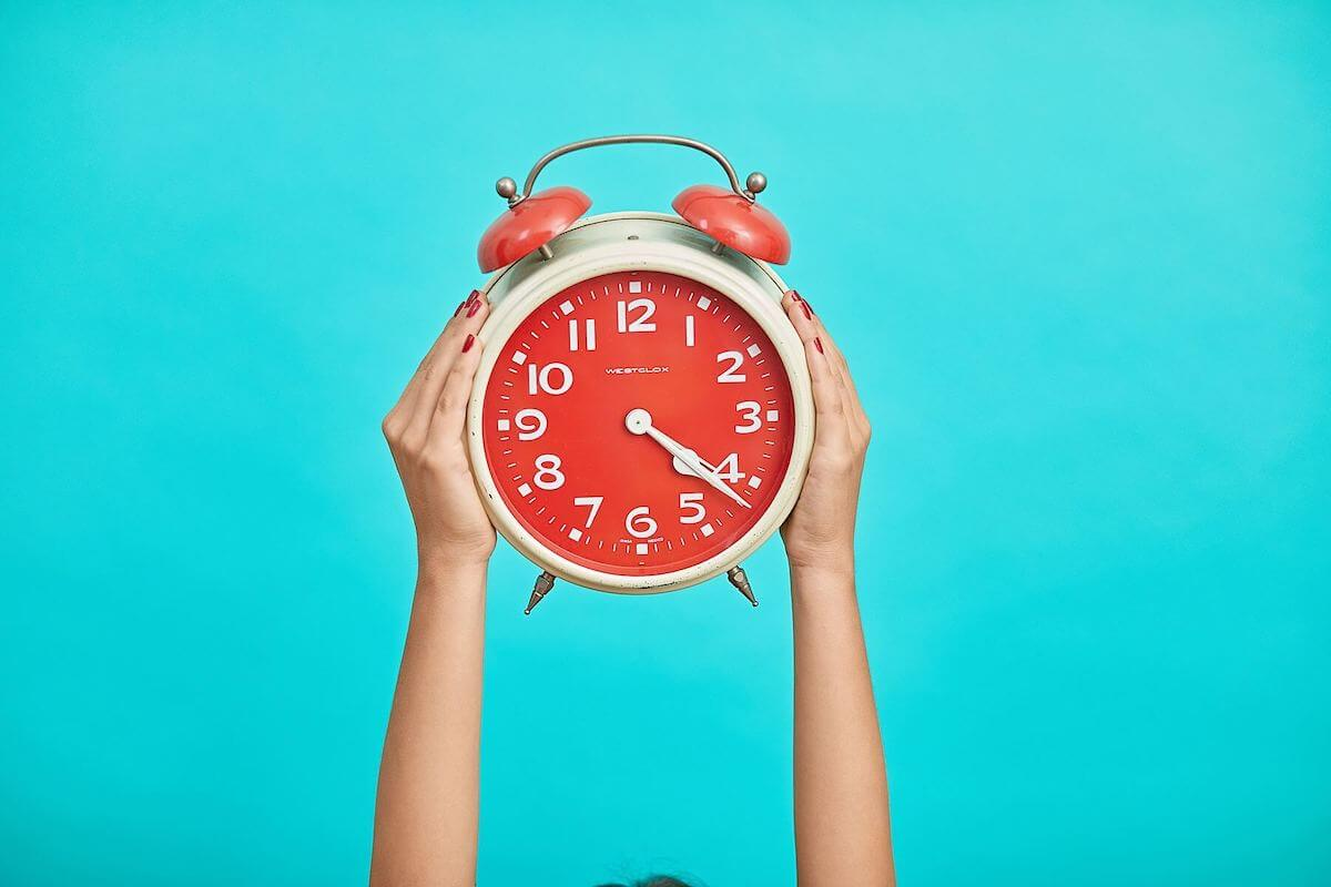 red clock on blue background time is of the essence for travel nurses
