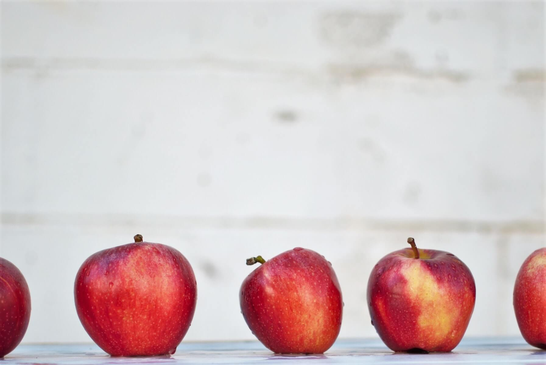row of red apples on retaining wall with blurry wall in background school nursing