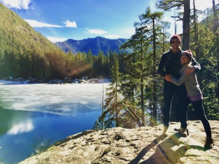photo of brit hamstra with partner standing on rock in front of lake and trees pediatric nurse