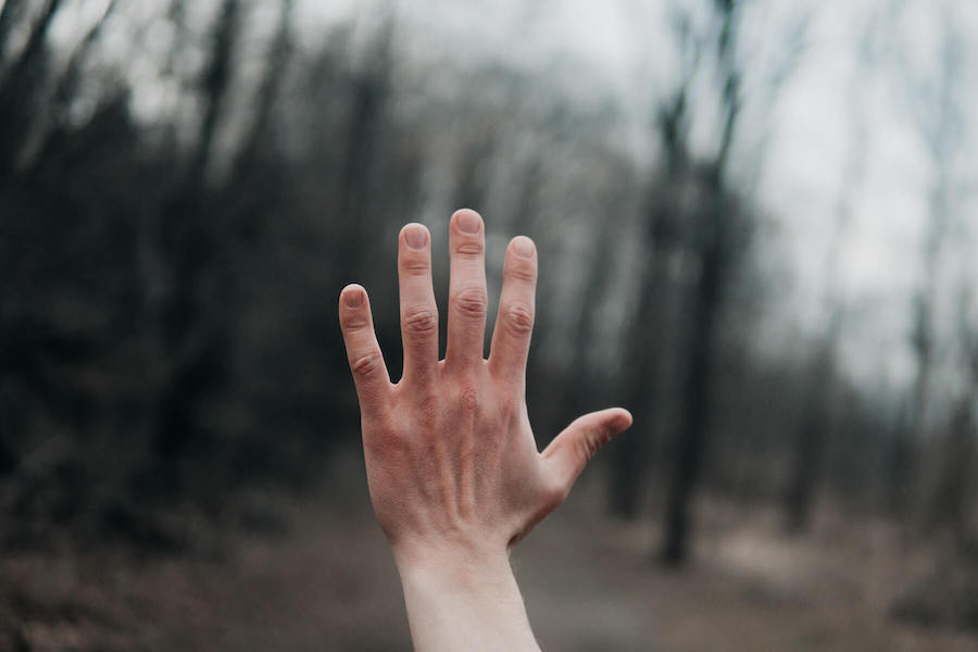 raised hand in front of blurred background nurse advocate