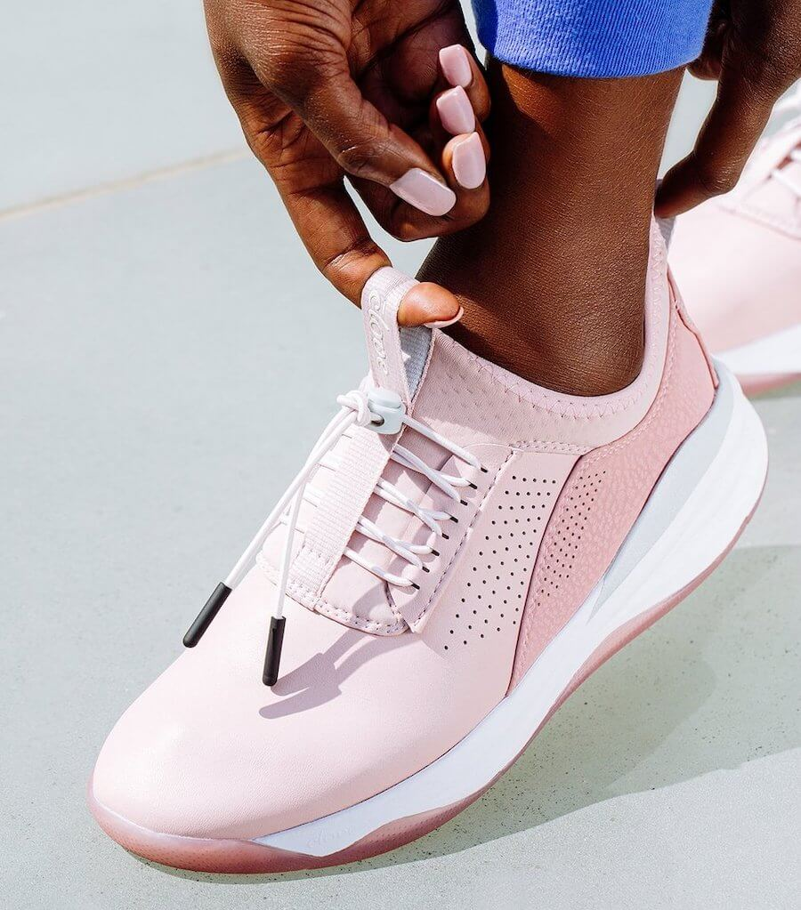 woman putting on pink nursing shoe clove nursing shoes holiday gift ideas for nurses