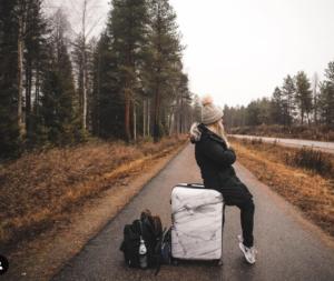 woman sitting on suitcase in road Kylee Nelson passportsandpreemies