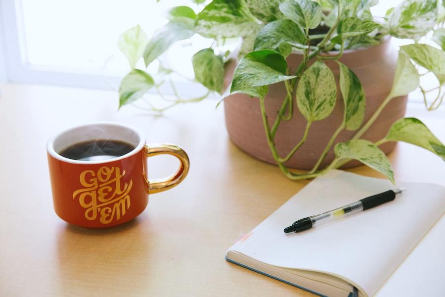 plant coffee cup and pen and paper on table side hustles for nurses