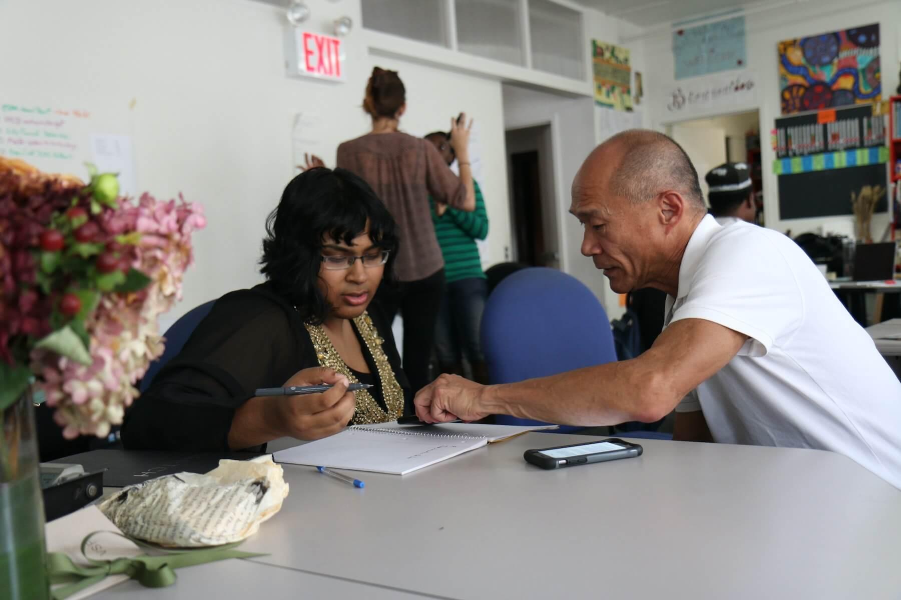 two people sitting at desk looking at notebook nurse mentorship