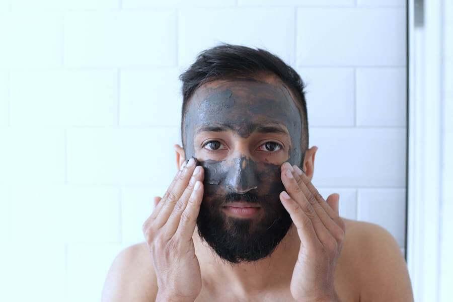 man looking in mirror applying face mask nurse skincare