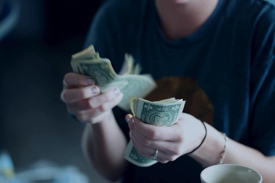woman flipping through dollar bills after selling scrubs nursing side hustles