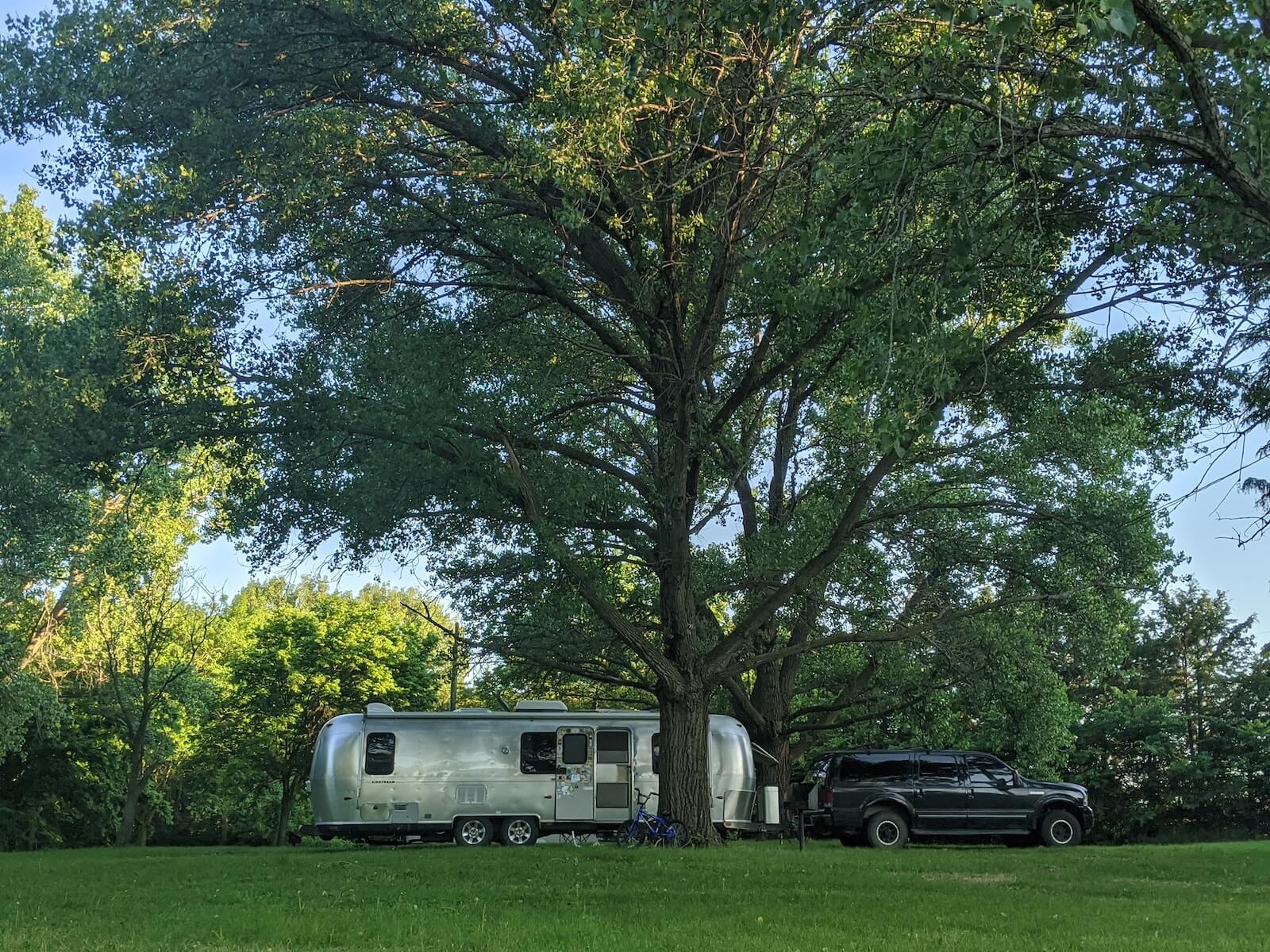 large truck and airstream rv parking underneath large tree with grassy field in the foreground travel nursing in an RV
