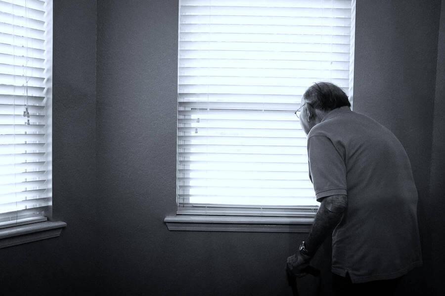 elderly man looking out of window in nursing home