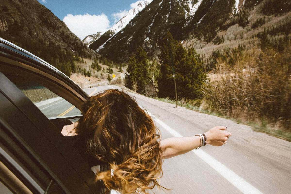 woman leaning out of car window driving up toward mountains travel nursing agencies choosing a travel nursing assignment