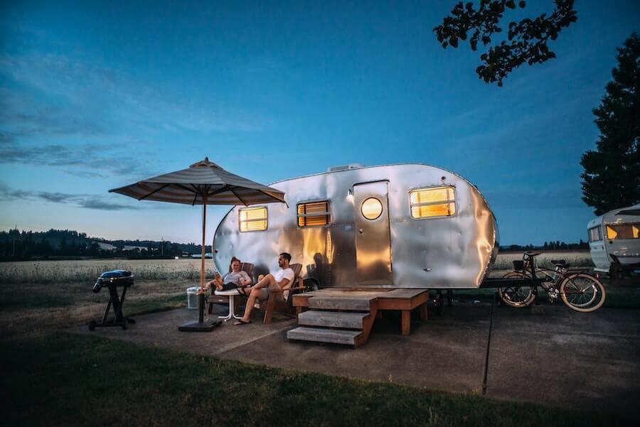 two people sitting outside camper van travel nursing housing from staff nurse to travel nurse