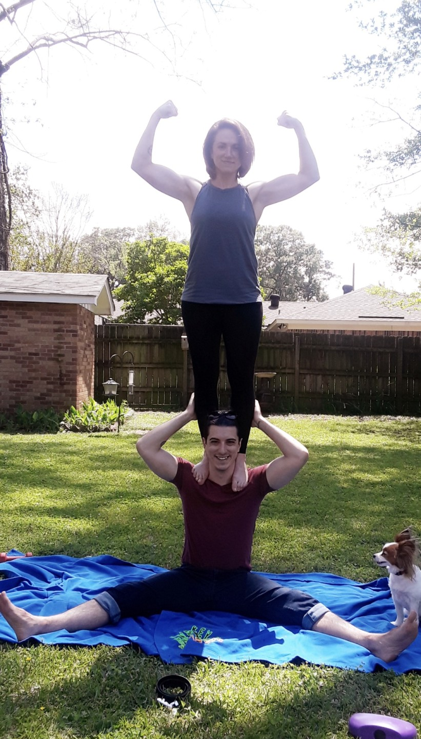 nurse ashley bowlin flexing while standing on man's shoulders