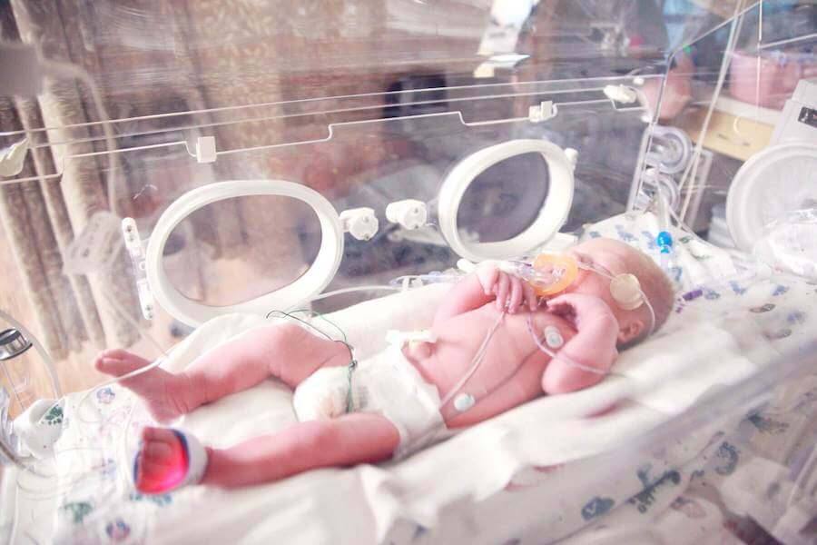 baby in incubator with cables attached neonatal nursing