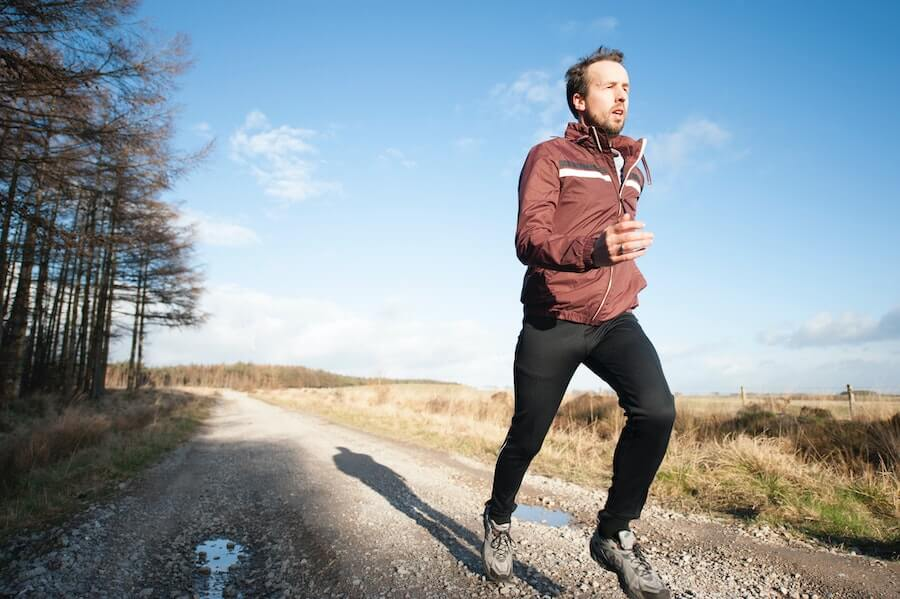 man jogging on country road health insurance for travel nurses