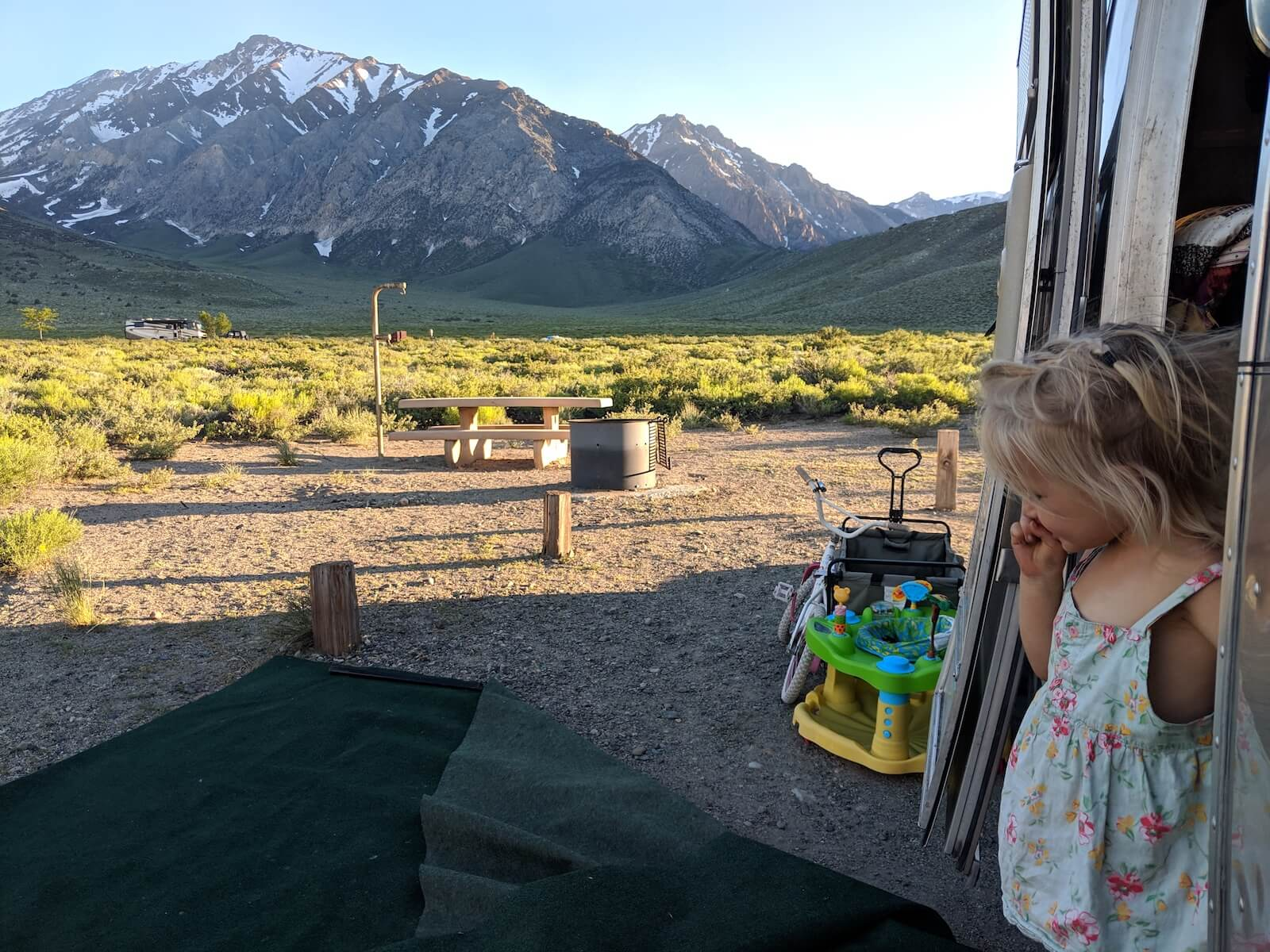 little girl stepping out of airstream door with mountains and grassy field in the background travel nursing in an RV