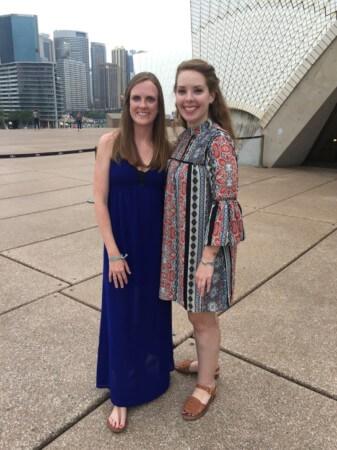 travel nurse duo nurses posing in front of modern building