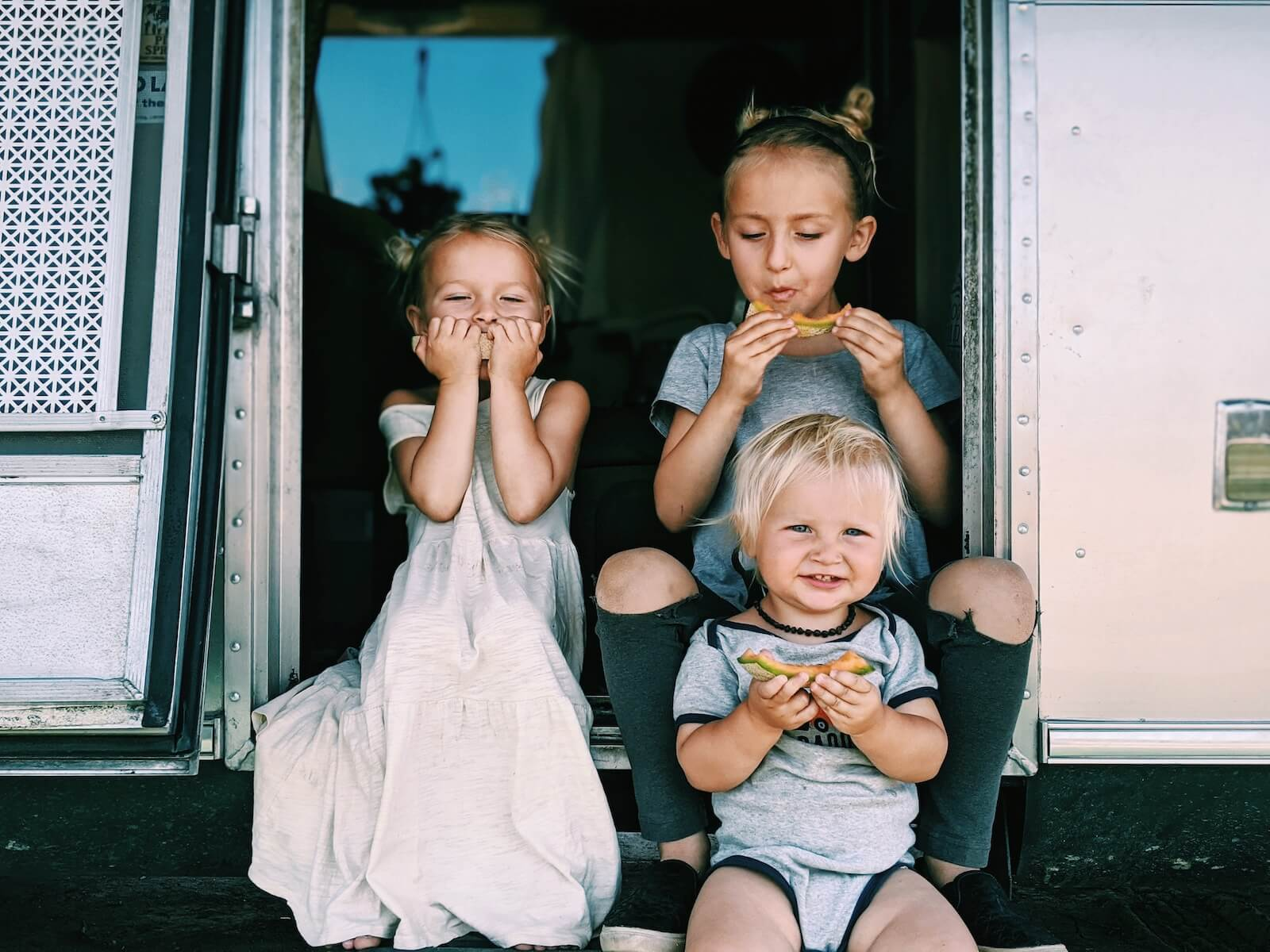 russ mortland children eating melon on the steps of their airstream travel nursing in an RV