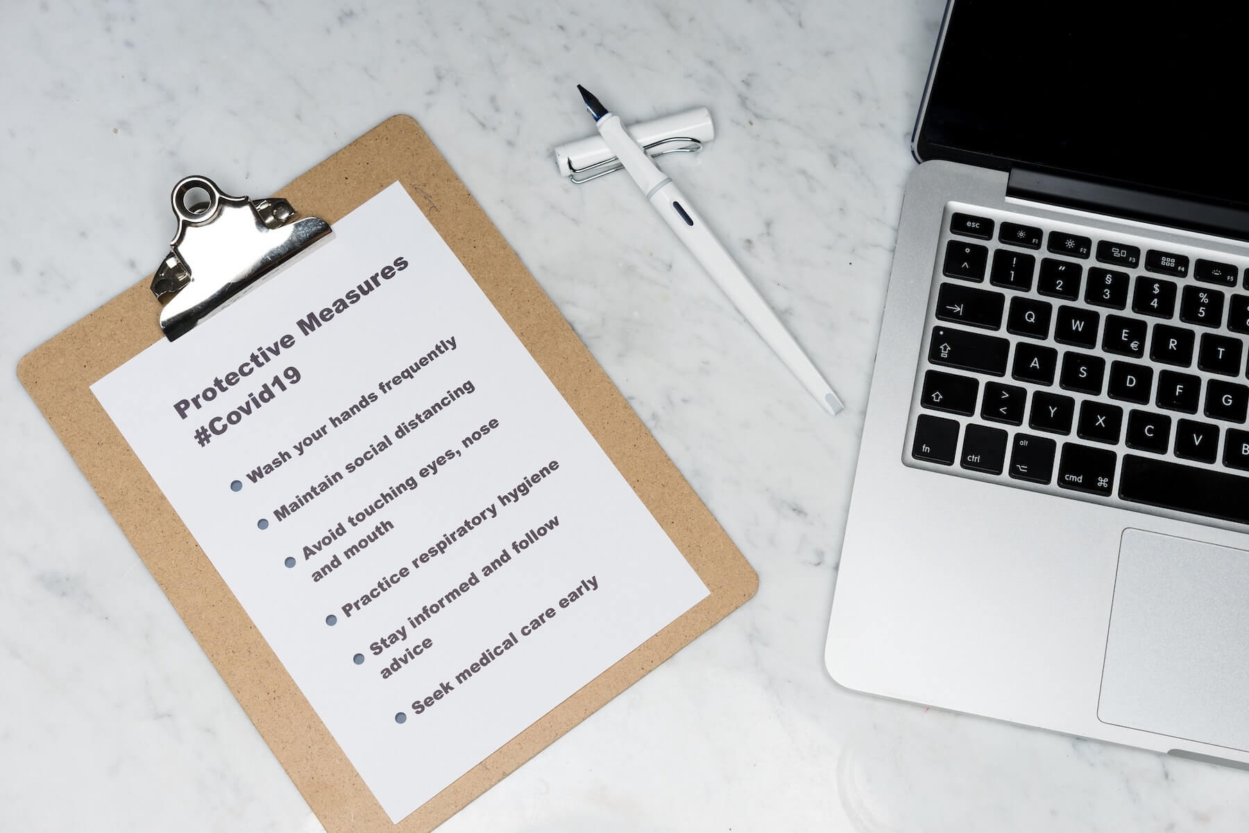 laptop and pen and clipboard with list of protective measures for covid19 on marble table nursing evidence based practice for nurses