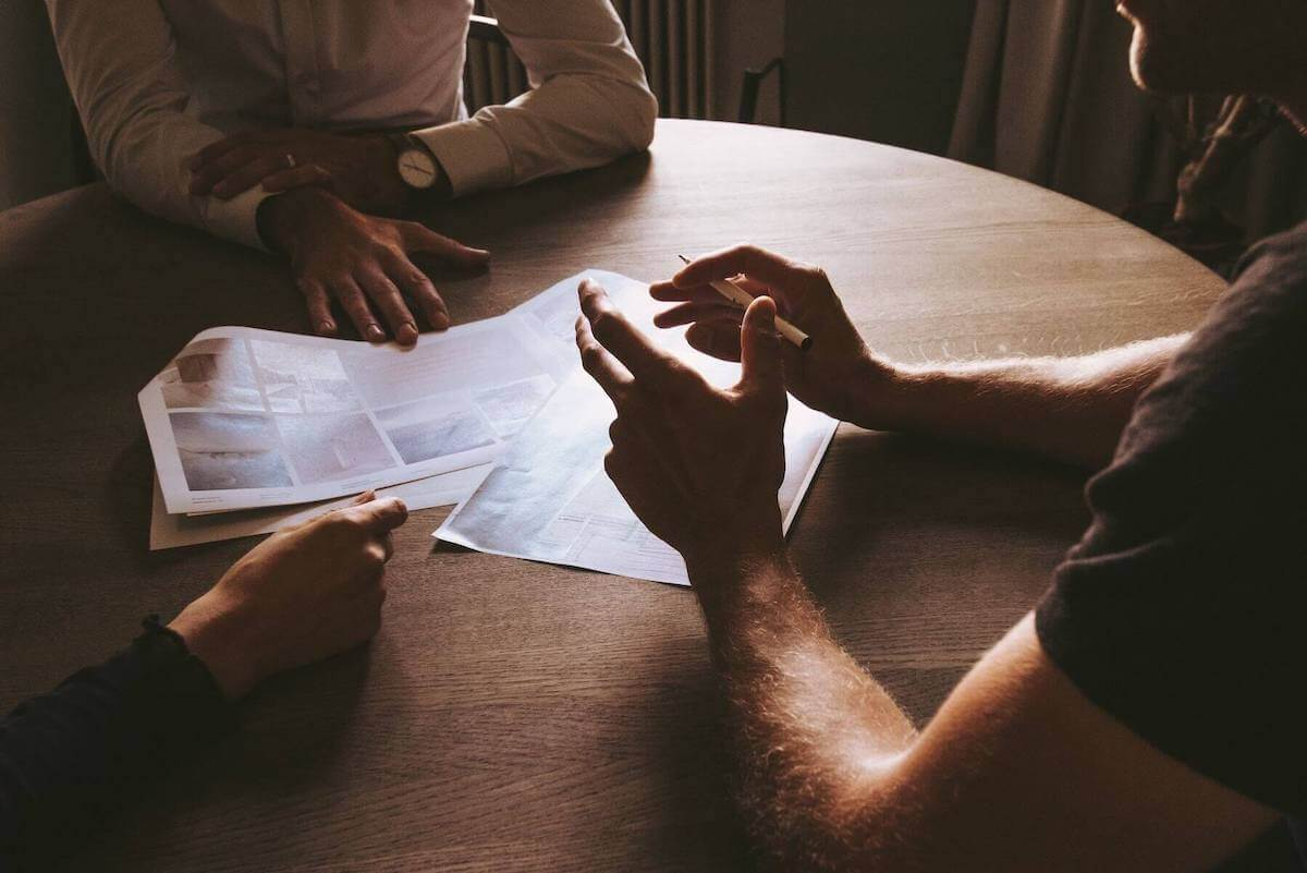 three people with hands on table discussing paperwork on table travel nursing agencies travel nursing contracts
