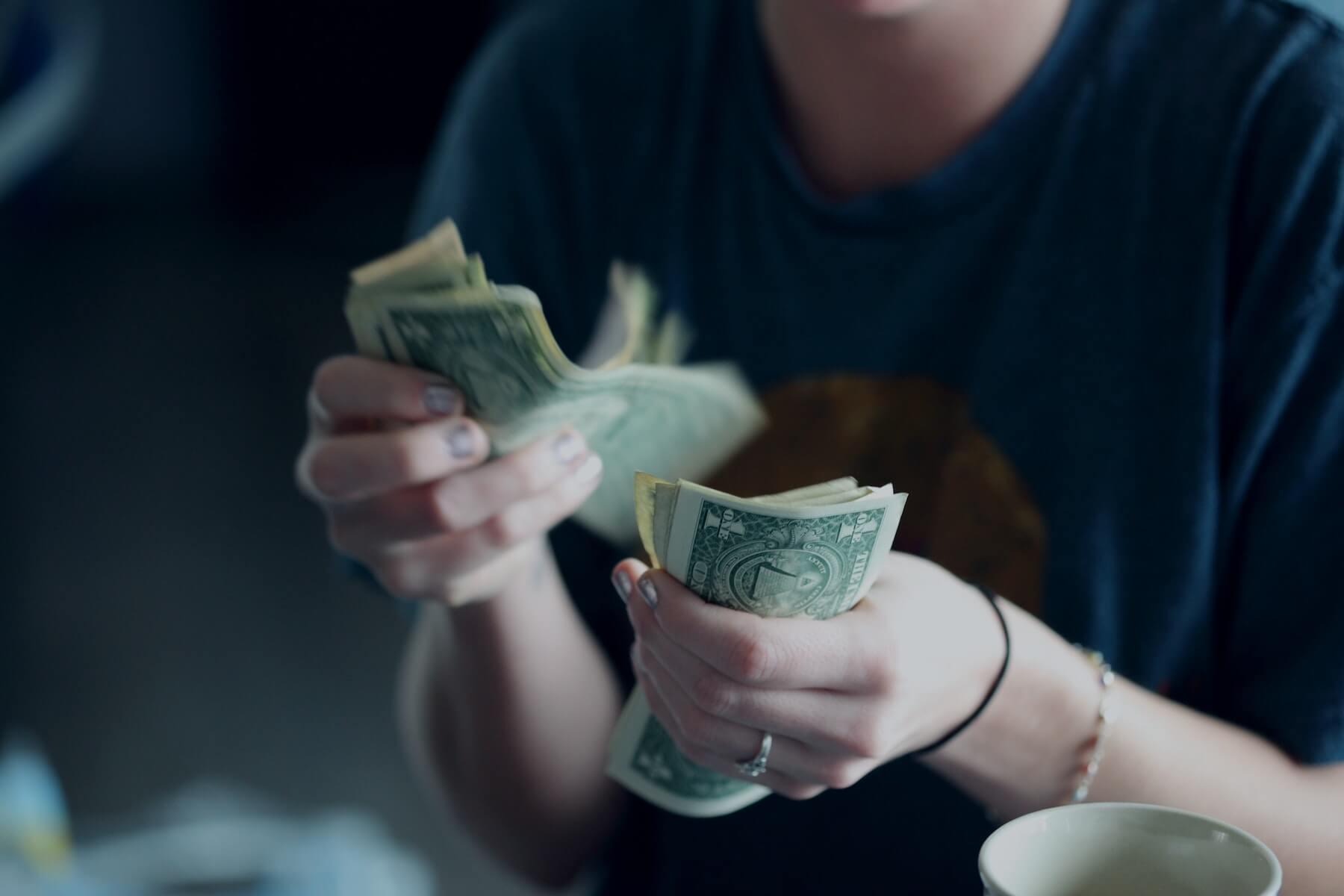 woman holding dollars in hand nursing pay decrease nursing during covid19