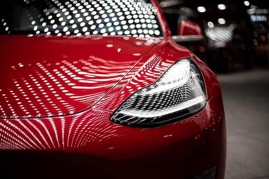 front photo of red tesla right headlight view how nurses can achieve financial freedom