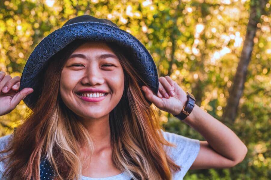 woman wearing hat smiling into camera how to transition from staff nurse to travel nurse