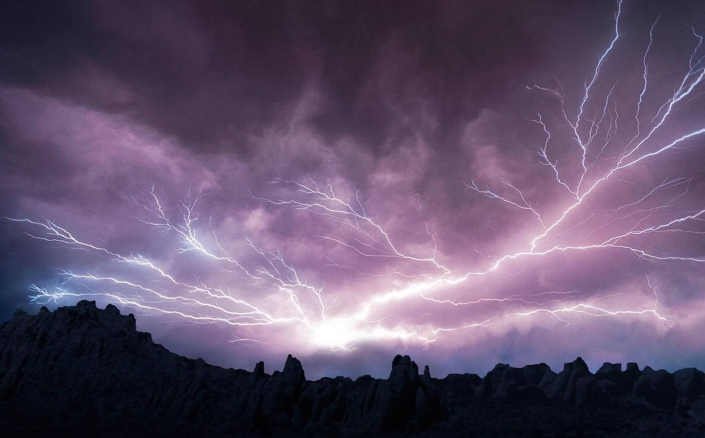 lightning striking in the sky with mountains on the horizon wilderness nursing
