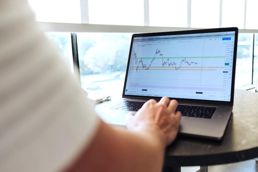 man typing on computer with graph of money over time nurse finances